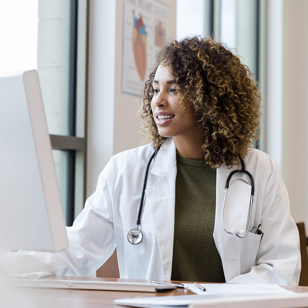 Mid adult female doctor reviews patient records on desktop PC