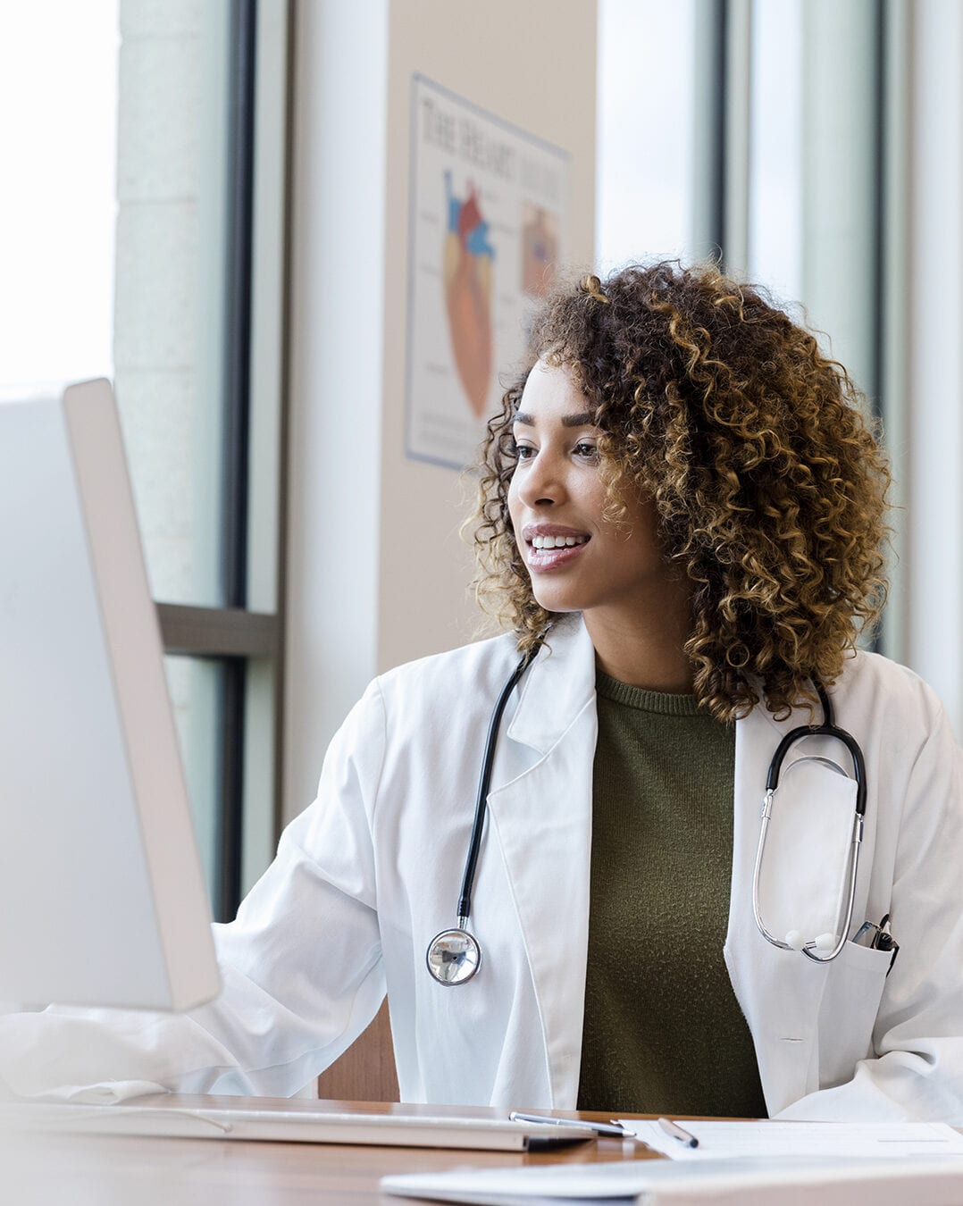 Doctor reviews patient records on desktop PC