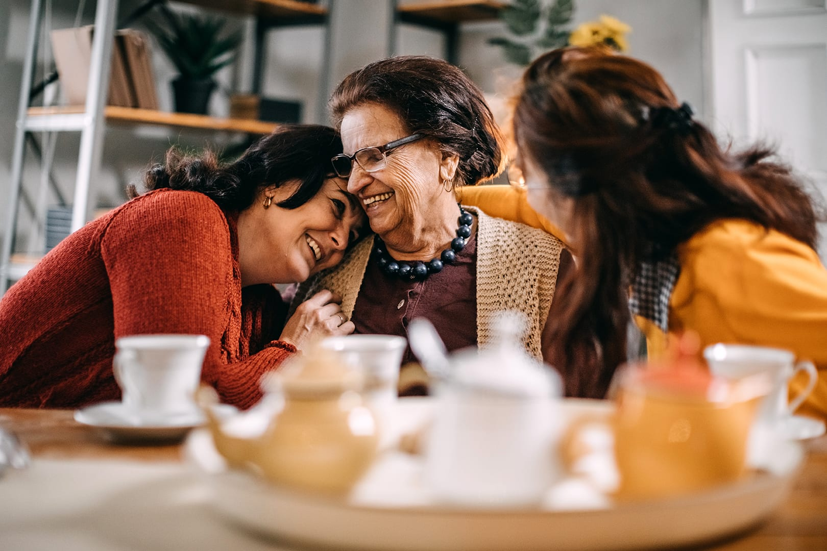 Older mother laughing with her two daughters